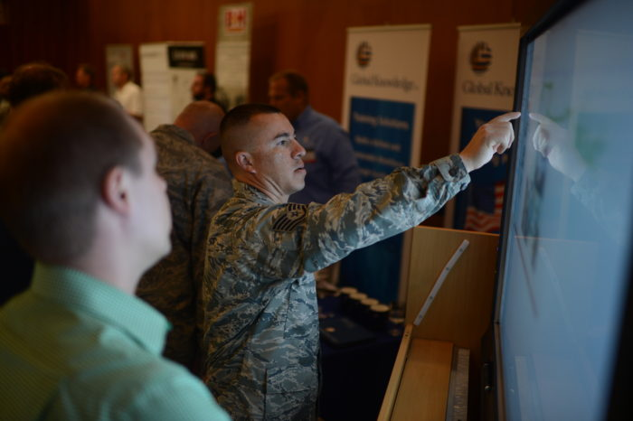U.S. Air Force Tech. Sgt. Reinhard Valleau, a 52nd Civil Engineer Squadron operations administrator from Orlando, Fla., interacts with a smart board at the 2014 Spangdahlem Technology Expo at Club Eifel, July 30, 2014. National Conference Services Inc. put on the event to allow military members to collaborate with their industry counterparts and discuss future expectations of technology and equipment. (U.S. Air Force photo by Senior Airman Gustavo Castillo/Released)